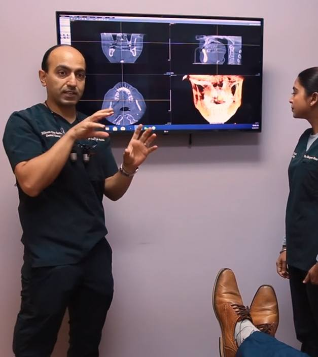 Dentists showing digital x-rays and treatment plan to dental patient