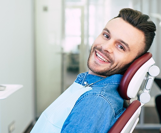 Man smiling in dental chair after dentistry treatment