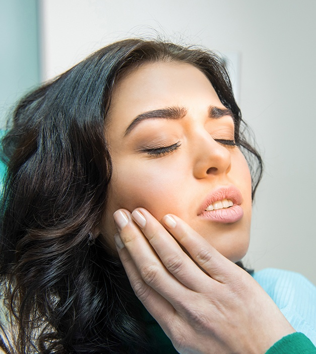 Woman holding jaw before wisdom tooth extraction