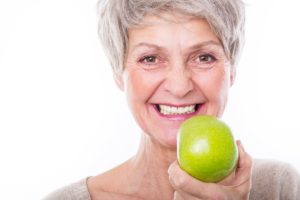 Woman with dental implants holding an apple.