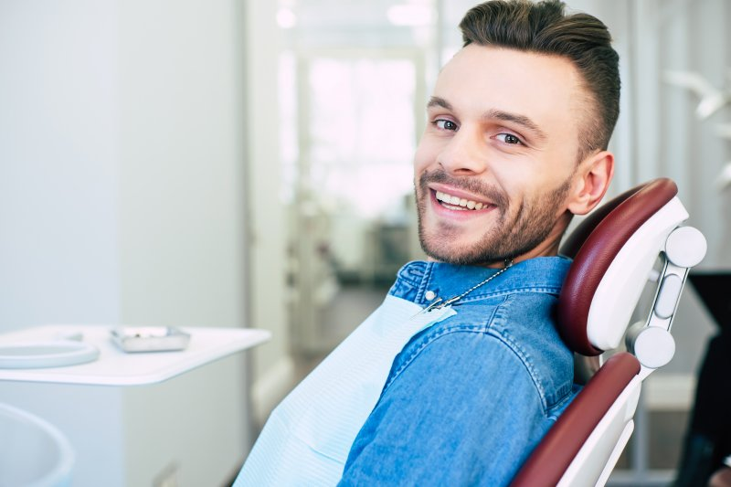 a young man wearing a denim shirt sits in the dentist's chair smiling while waiting to learn if he's a candidate for general anesthesia